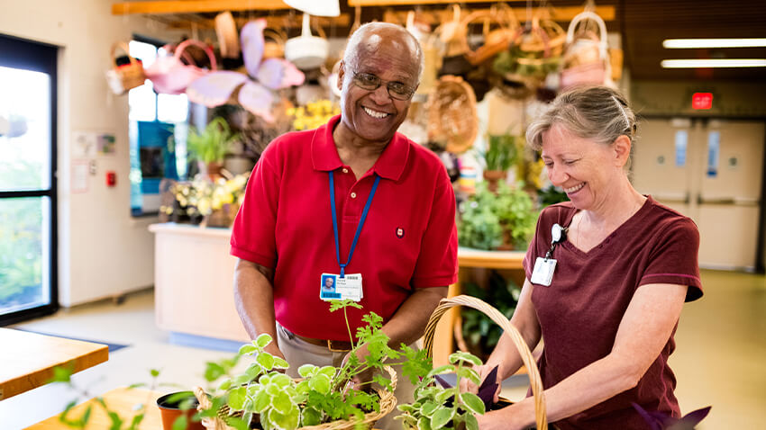 Older black man arranging plants with middle-aged white woman, both smiling