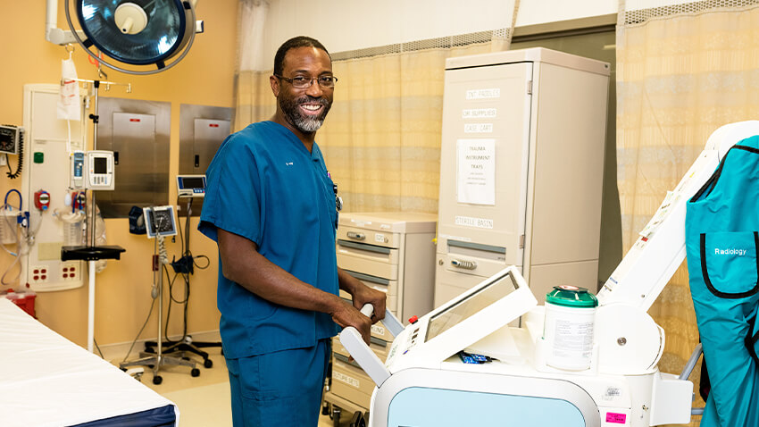 Clinician smiling at camera, standing with diagnostic equipment