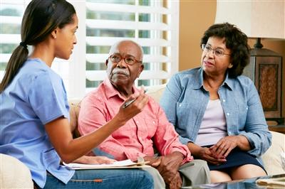 Home care nurse talking with senior couple at home