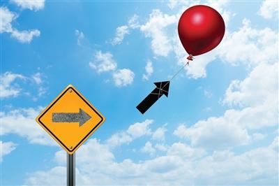 Red balloon tied to black arrow and floating it away from the yellow sign that it seems to have been pulled from