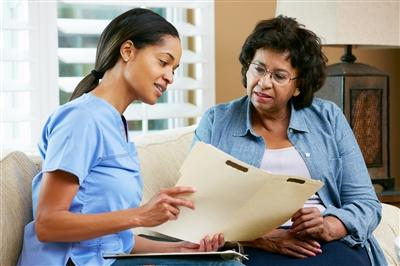 Nurse sitting with older woman going over information in file in nurse's hand