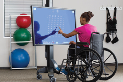 Woman sitting in a wheelchair using the bioness technology