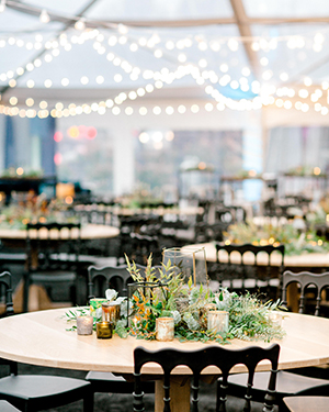 View over event room of tables with overhead string lighting