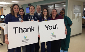 group of nurses holding thank you signs