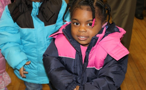child in warm, pink and black winter coat