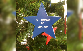 close up on a star that says In memory of pap-pap on the tree of lights