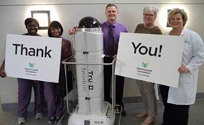 Tru-D machine with some hospital staff holding thank you signs
