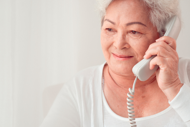 mature woman using corded phone