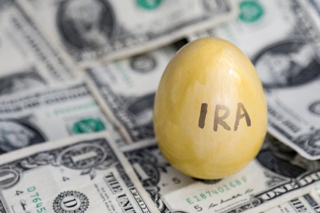 Gold painted egg with IRA written on it on top of dollar bills