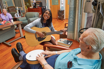 Music therapist playing guitar and working with man who has a small drum in lap