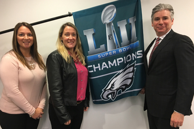 (L to R) Melissa Bateman, UAS; Meghan Sayer, Paoli Hospital Foundation; and Scott Elkins, president of UAS, celebrate the Eagles victory.