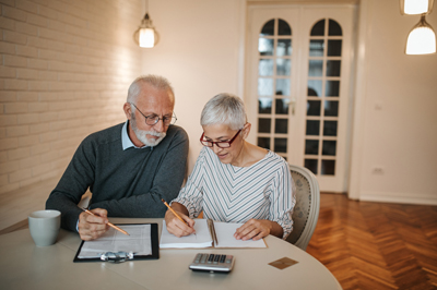 Older couple sitting at table planning expenses