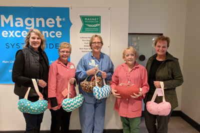 GFWC Junior Women's Club of Springfield members holding some of the donated hand-crafted comfort pillows