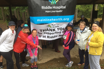 Group of ladies standing next to the Riddle Hospital logo and thank you for supporting the NICU at Riddle sign