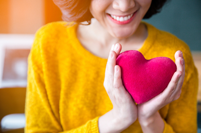 Woman holding plush red heart