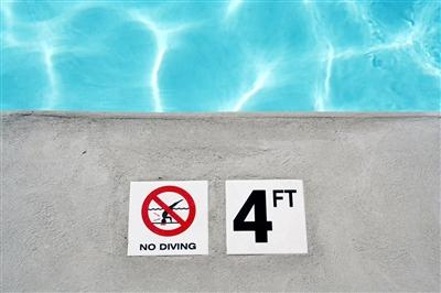 4ft no diving sign on ground next to pool