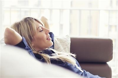 Woman reclining on couch with hands behind head