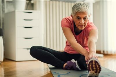 Older woman stretching on a yoga mat