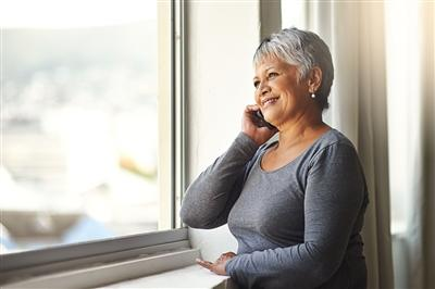 Older woman on the phone sitting next to a window