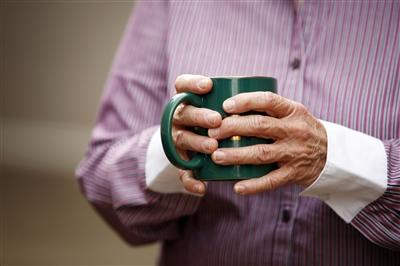 Older hands holding a mug