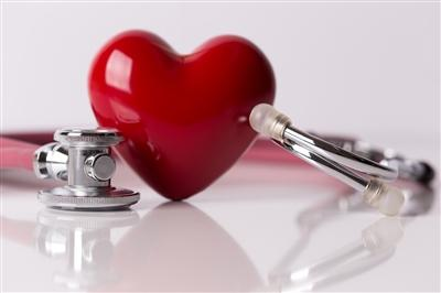 Plastic red heart sitting on table with stethoscope