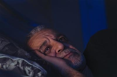 Man laying in bed awake