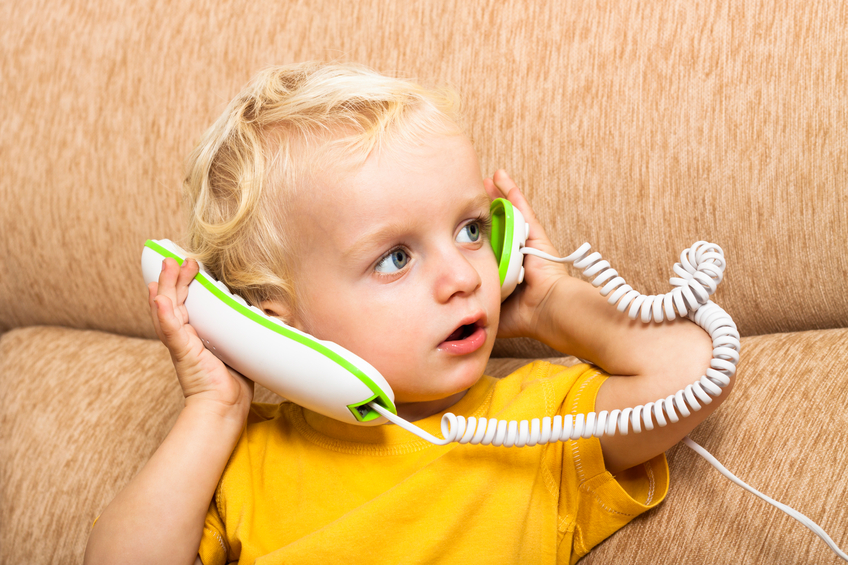 young child playing with corded phone