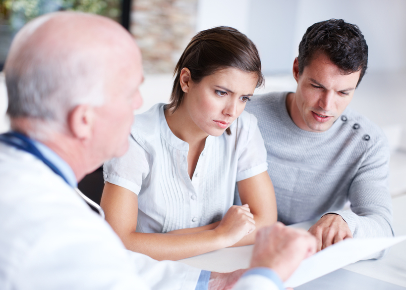 young adult couple looking forlorn while talking with doctor