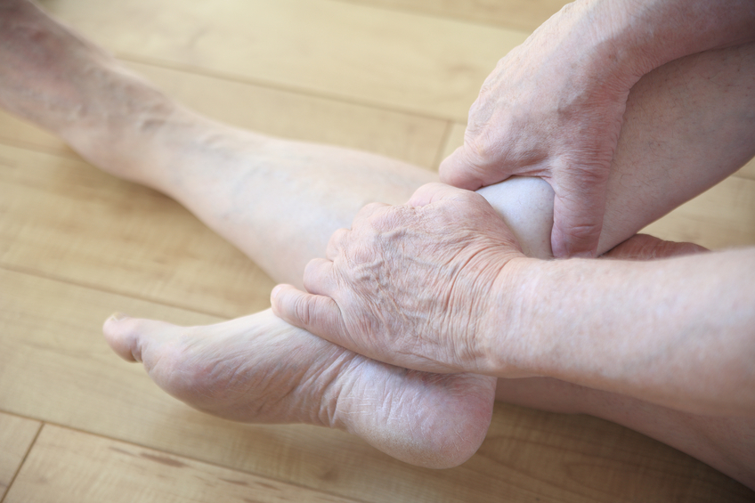 person cradling lower leg and ankle in their hands