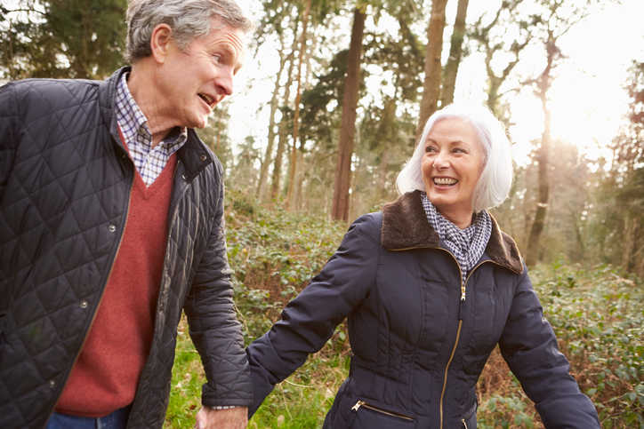 Older couple walking in woods