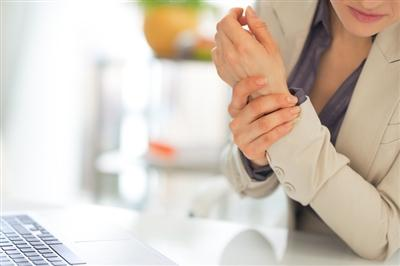 Woman grasping hand in pain