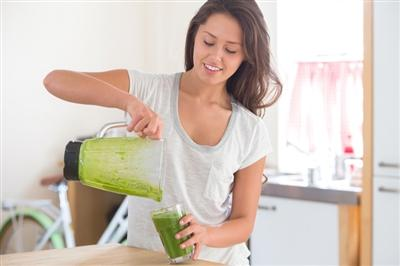 Woman pour a green smoothie into a glass from a blender