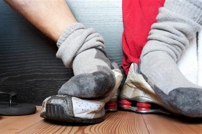 Sock covered feet resting on top of sneakers