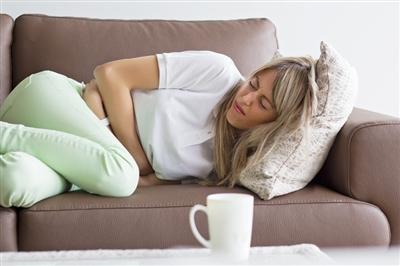 Young female curled up in pain on a couch