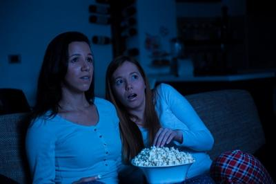 Two women watching tv together, horror movie