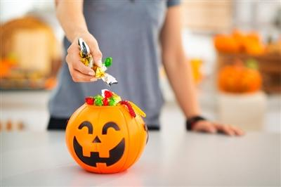 Person grabbing a handful of candy from a little plastic jack 'o lantern on a counter top