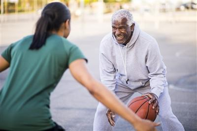 Young adult woman and older gentleman playing basketball outside