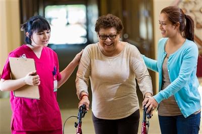 Therapists helping woman walk with a walker