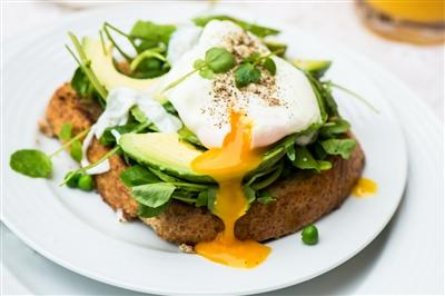 Poached egg, parsley and avocado on toast on a plate