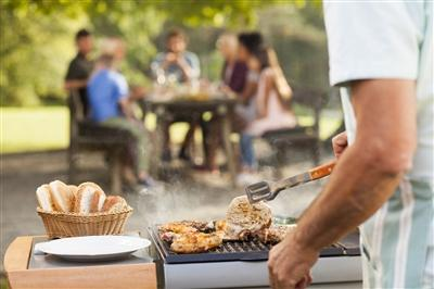 Close-up on person grilling food with table of people in the background