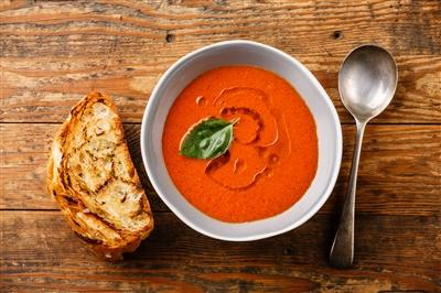 Gazpacho in a bowl on a wood plank table surrounded by a spoon and piece of toasted bread