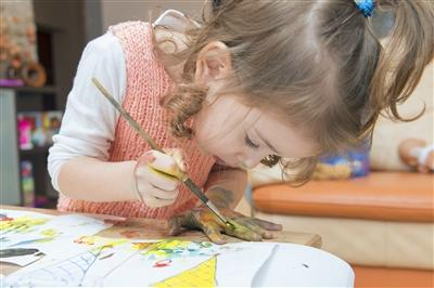 Little girl carefully painting at a table