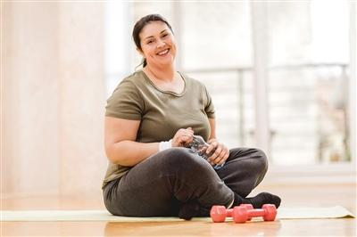 Woman sitting on yoga mat holding her water bottle with small weights sitting in front of her