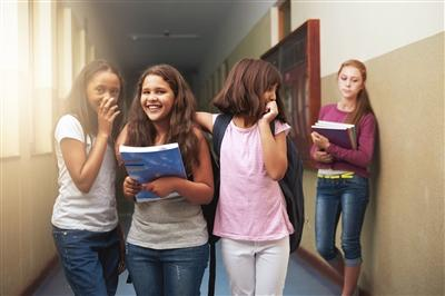 Three girls whispering and laughing while a fourth girls leans against the wall in the background looking upset