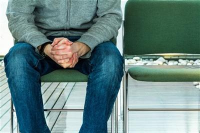Close-up on a man sitting in a chair in a waiting room with his hands folded in his lap