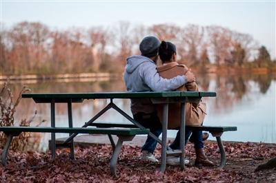 Couple comforting each other on park bench