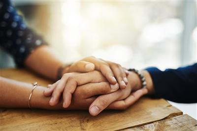 People comforting one another (picture shows close up on their clasped hands on a table)