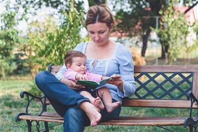 Mom reading to baby on park bench