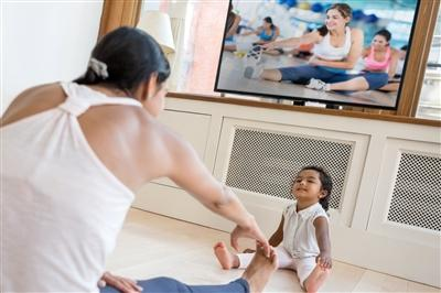 Woman exercising in her living room with toddler