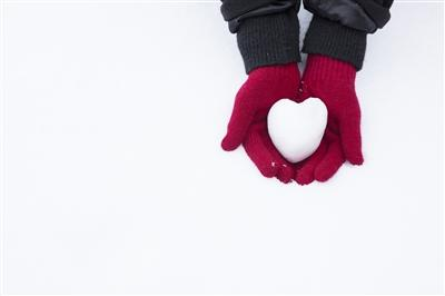Close-up of glove-covered hands cupping a heart-shaped snow ball outside